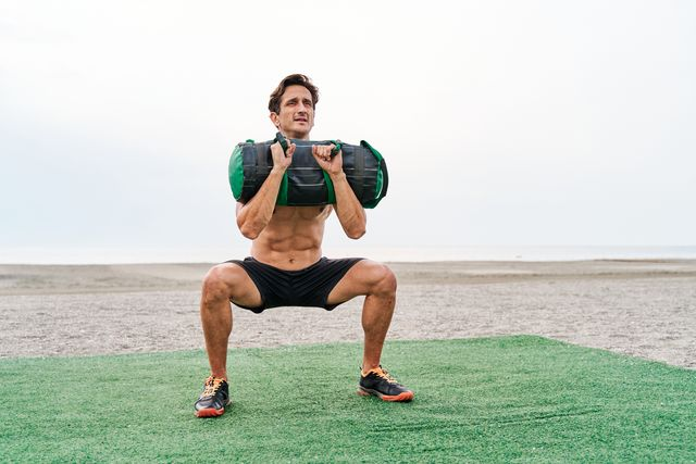 young muscular man training on the beach shirtless doing a front squat lifting a sandbag