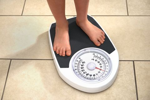 Young Obese Boy on Bathroom Scales