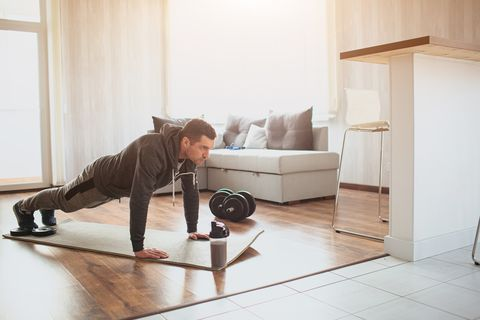 young ordinary man go in for sport at home full size picture of regular ordinary guy stand in plank position alone in room beginner try to do his best and exercise hardworking real person
