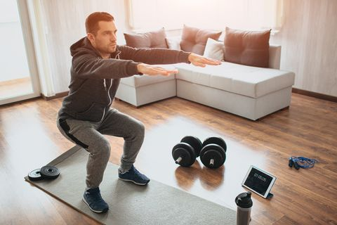 young ordinary man go in for sport at home real picture of egular guy doing squats with stretch hands forward beginner or amateur has workout in apartment sport equipment on floor