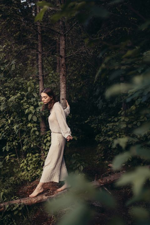 young pensive woman walking in forest