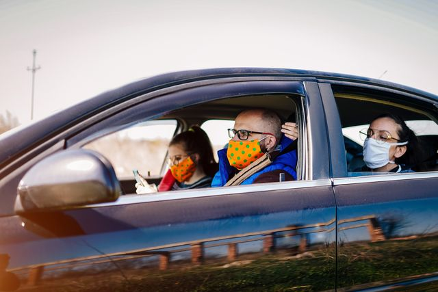 covid 19, young people wearing disposable face mask while driving