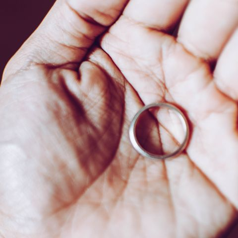 A young person is holding a wedding ring