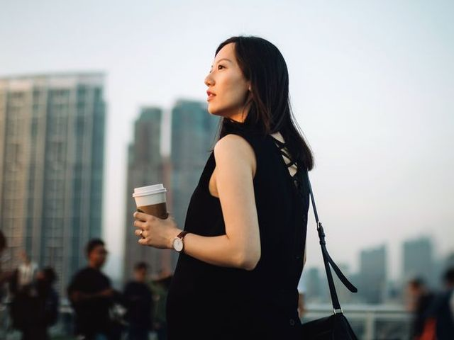 young pregnant woman having coffee and relaxing in city, looking towards the beautiful sky at sunset