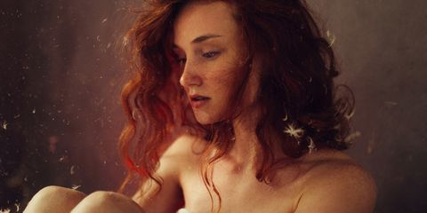 Young redhead woman with feathers falling around