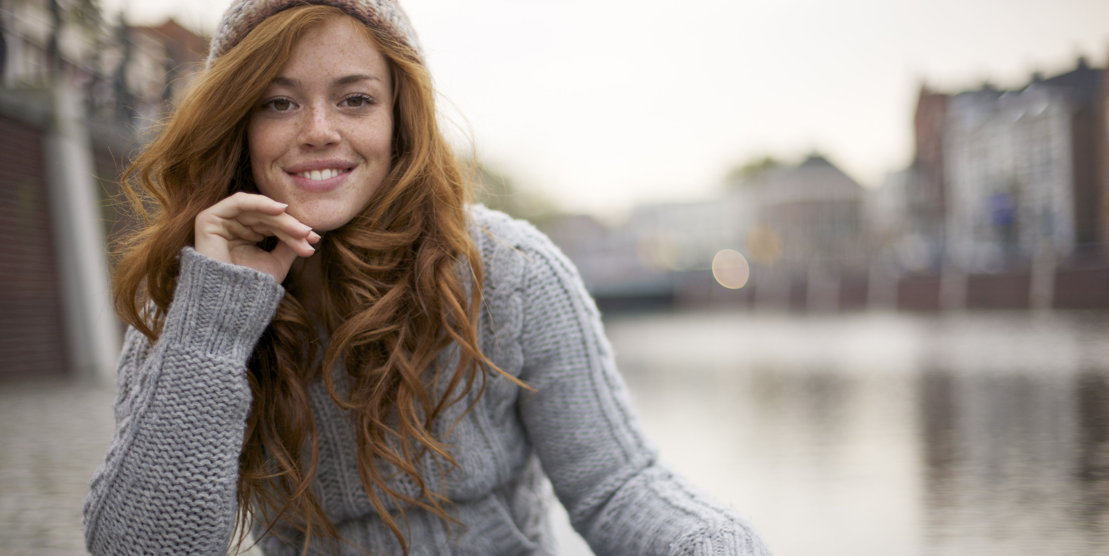 Young Redheaded Woman in a Grey Knit Jumper at the Canal