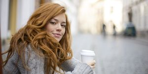 Young Redheaded Woman with Coffee To Go