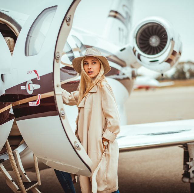 young rich blonde female looking over her shoulder while entering a private airplane parked on an airport tarmac