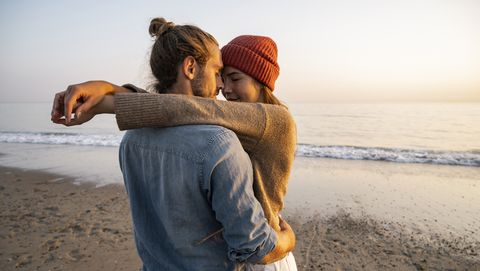 young romantic couple standing face to face at beach against clear sky during sunset