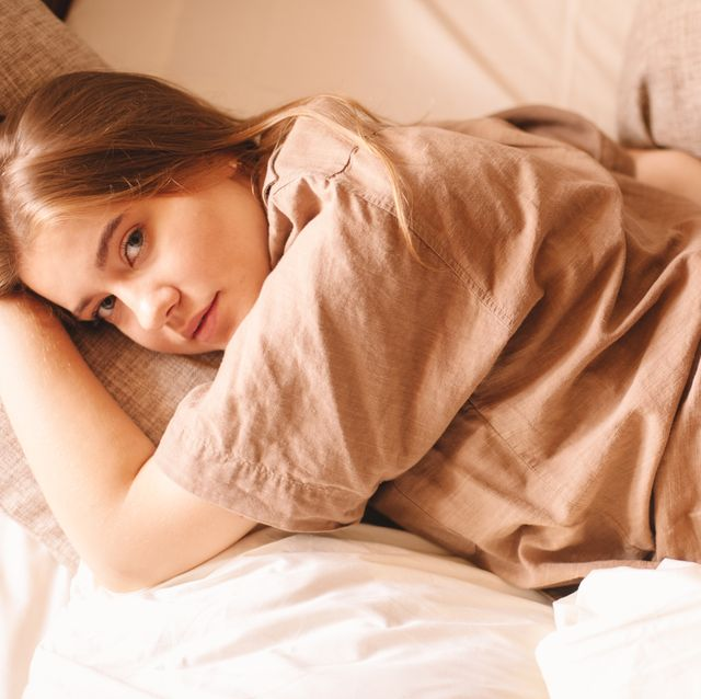 young sensual woman lying in bed at home