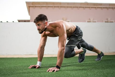 Young shirtless muscular man warming up before a workout outdoors.
