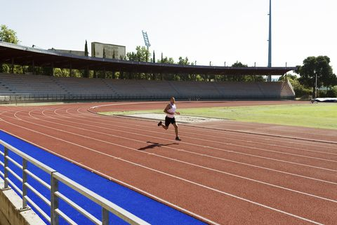 young sportsman running on tartan track