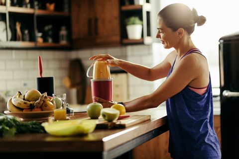 young sportswoman making healthy smoothie in the kitchen