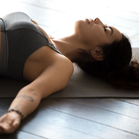young sporty attractive woman practicing yoga, dead body pose