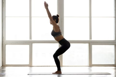 Young sporty attractive woman practicing yoga, doing Chair exercise
