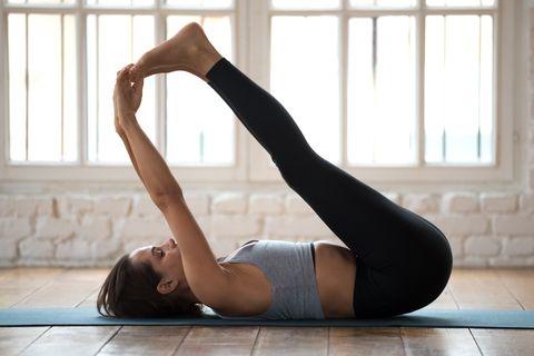 Young sporty attractive woman practicing yoga, Urdhva Prasarita Padasana exercise