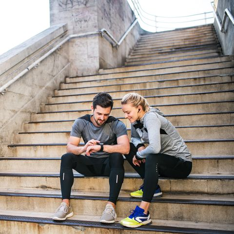 Young sporty man and woman with earphones sitting on stairs outside in a city, using smart watch.