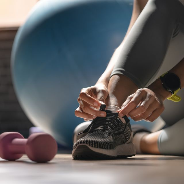 young sporty woman with smart watch tying shoelaces in fitness