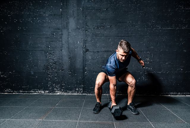 young strong fit muscular sweaty man with big muscles strength cross workout training with dumbbells weights in the gym dark image with shadows real people