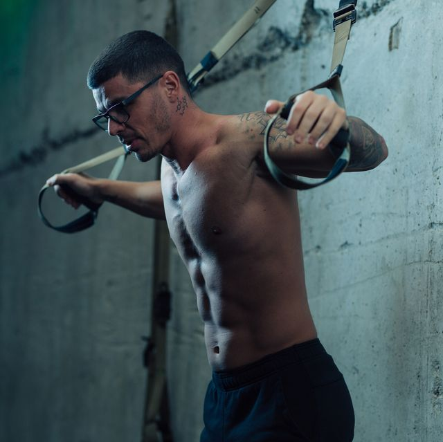 Young strong man in gym doing suspended exercises with straps in the gym
