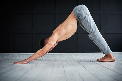 young strong shirtless man practices yoga at the yoga studio