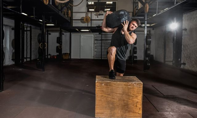 young strong sweaty fit muscular man with big muscles holding heavy sandbag on his shoulder with his hands and climb on the jump box for legs cross workout training in the gym