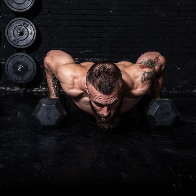young sweaty strong fit muscular man with big muscles doing push ups on the dumbbells in the gym as hardcore cross workout training with free copy space