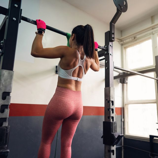 young unrecognizable fit woman doing resistance band assisted pullups in gym