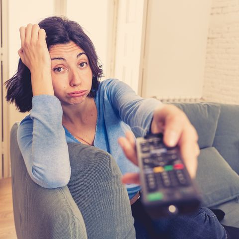 young upset woman on sofa using control remote zapping bored of bad tv shows and programing  looking disinterested, aloof and sleepless people, too much bad television and sedentary lifestyle
