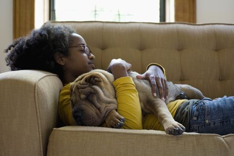 a young woman and her shar pei napping on a couch