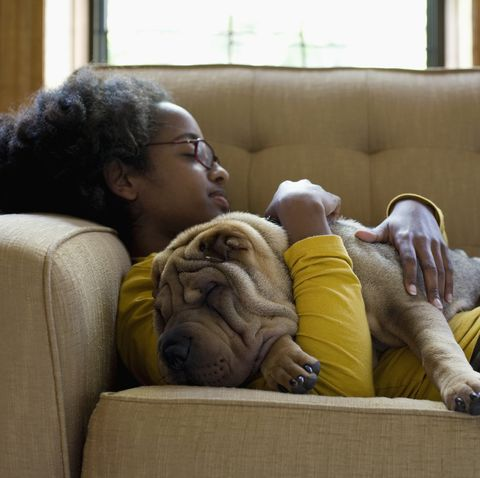 a young woman and her sharpei napping on a couch