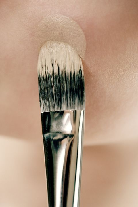 Young woman applying foundation with make-up brush, close-up