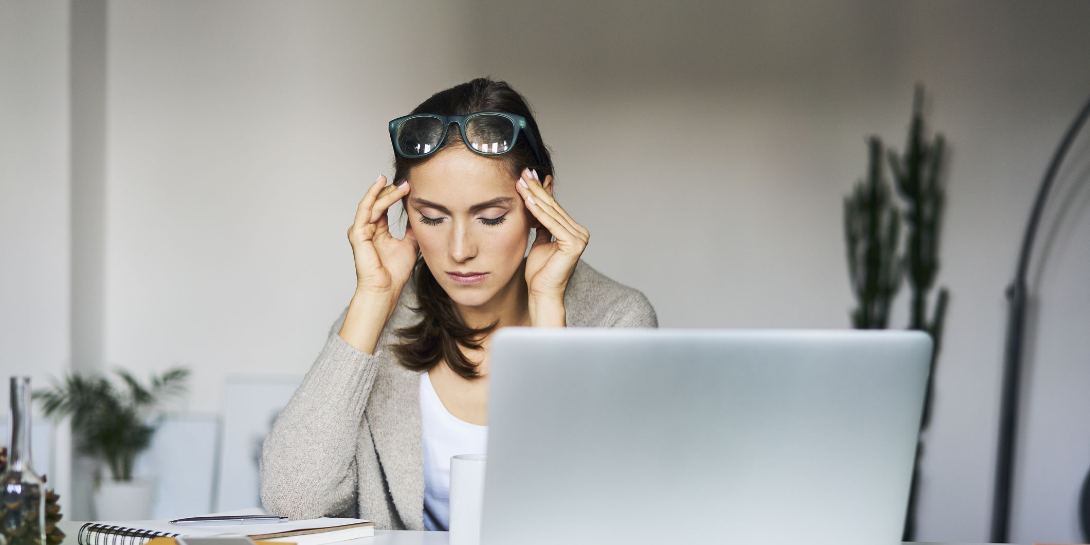 Young woman at home with laptop on desk touching her temples