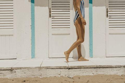 Mujer en la playa con bañador de rayas.