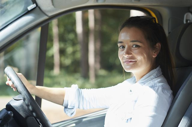 young woman at the driving wheel of her camper van