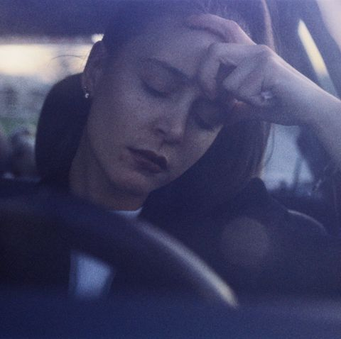 young woman at wheel of car, eyes closed, with hand on head grainy