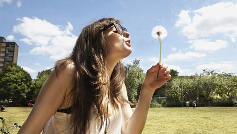young woman blowing away the dandelion seeds