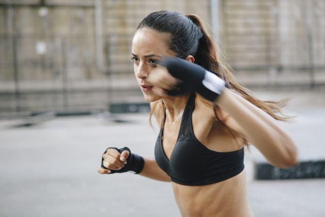young woman boxing in urban setting