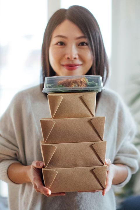 young woman carrying takeaway food boxes