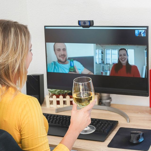 young woman chatting with friends drinking wine and laughing together   alternative party during home isolation quarantine   focus on glass hand