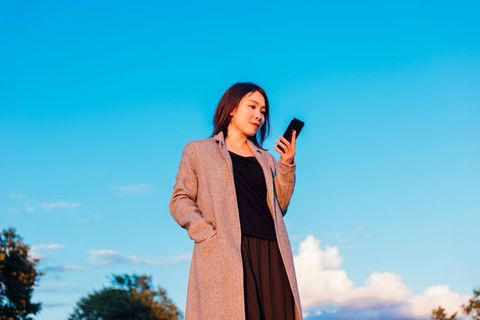 young woman checking emails on smartphone against clear blue sky
