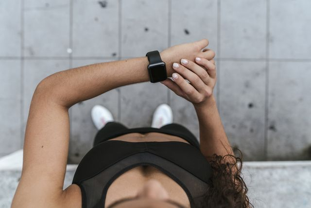 young woman checking smartwatch outdoors