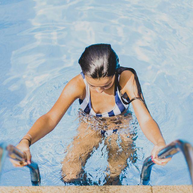 young woman climbing down in swimming pool