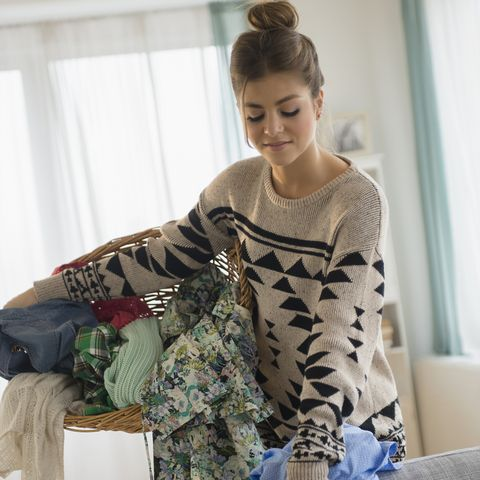 Young woman collecting clothes for laundry