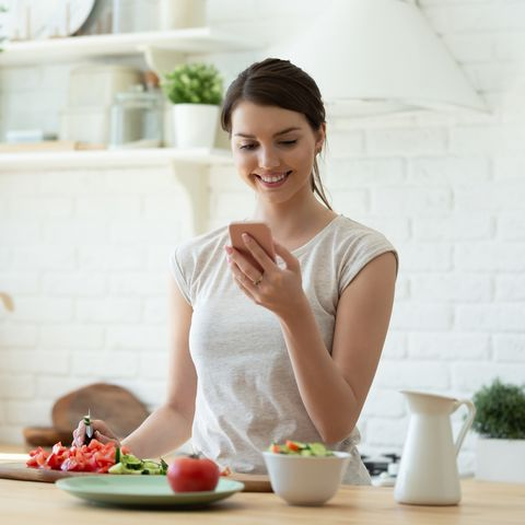young woman cooking and using mobile phone