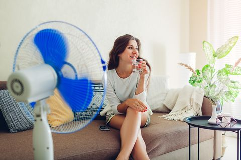 young woman cooling down by ventilator at home while drinking water and hanging in phone summer heat