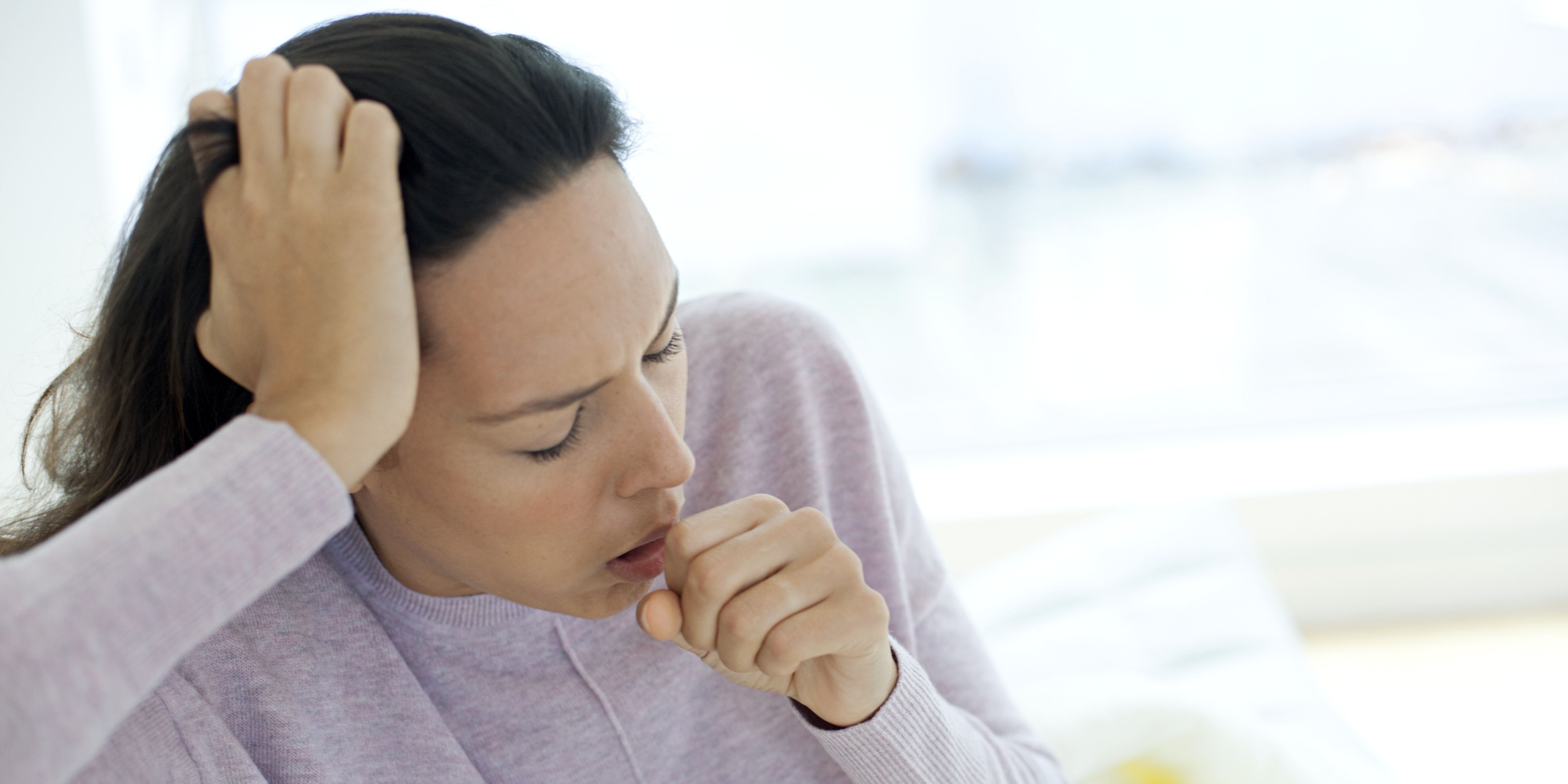 Young woman coughing, common stages of a cold