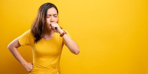 Young Woman Coughing While Sitting Against Yellow Background