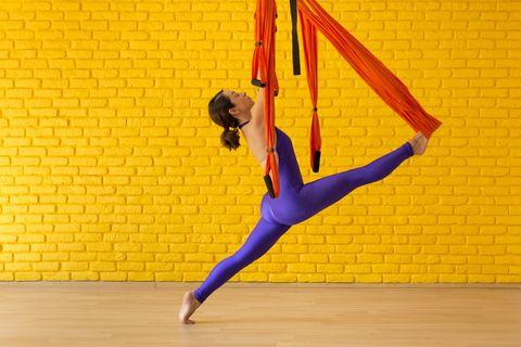 young woman doing antigravity yoga