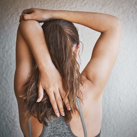 Young woman doing arm stretches as pre-exercise warm-up